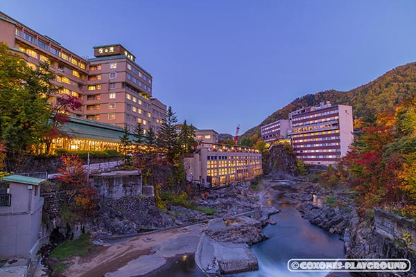 日没直前の月見橋から望む定山渓温泉街の旅館と紅葉