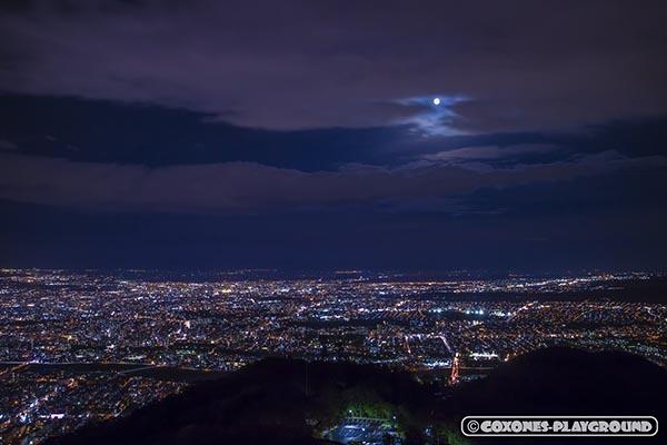 漆黒の空に浮かぶ月寒方面の夜景と満月