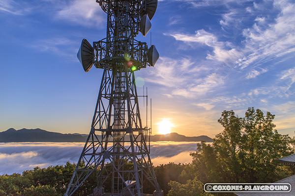 山頂の鉄塔と雲海と沈みゆく夕日