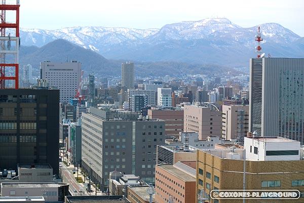 展望回廊から望む札幌市中心部の街並みと雪がまだ残る手稲山